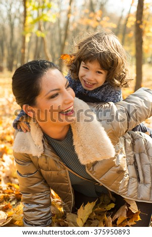Cheerful mother and her toddler son having fun in autumn park