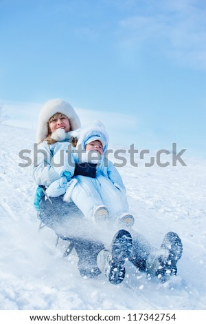Cheerful mother and her toddler son sliding down the winter hill - stock photo