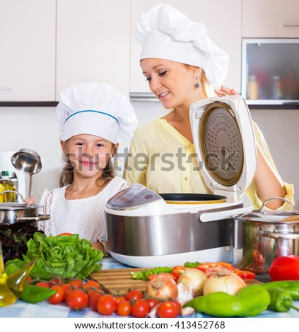 Cheerful mother and little girl preparing vegetables in slow-cooker - stock photo
