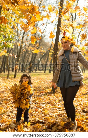 Cheerful mother and son tossing autumn leaves in park and having fun together