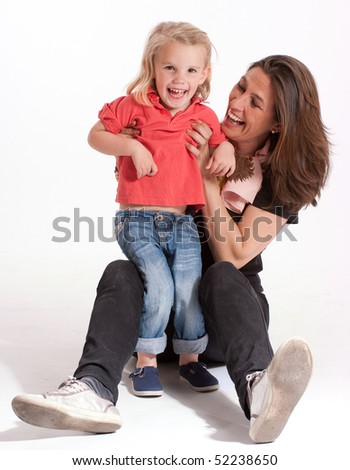 Cheerful mother holding a cute blonde little girl