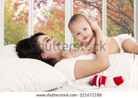 Cheerful mother hugging her baby girl on bedroom at leisure time in autumn day - stock photo