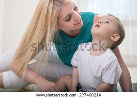Cheerful mother is sitting with her son on the flooring. The mom is looking at her child and smiling. The boy is looking up with interest - stock photo