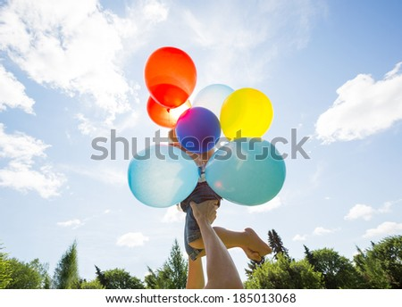 Cheerful mother lifting daughter holding colorful balloons against cloudy sky - stock photo