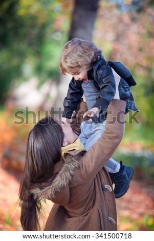 Cheerful mother raising her son high up and having fun with him in autumn park. - stock photo