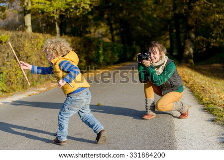 Cheerful mother taking picture of her cute little son in the park, happy young family having fun outdoors, parental love and enjoyment  - stock photo