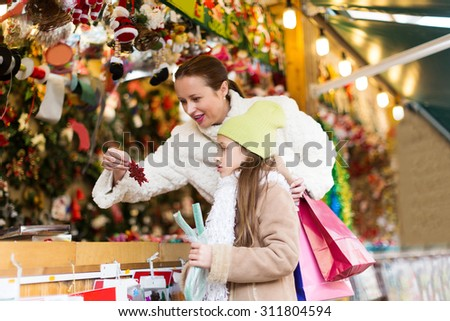 cheerful mother with a little daughter choose decorations for the Christmas tree. Focus on girl - stock photo