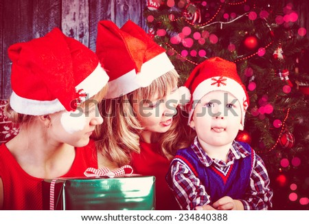 Cheerful mother with her son and daughter showing tongues at Christmas time - stock photo