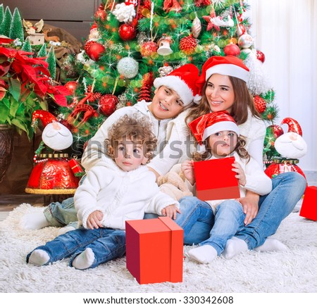 Cheerful mother with her three precious kids wearing red Santa hats sitting near beautiful decorated Christmas tree, happy family holiday