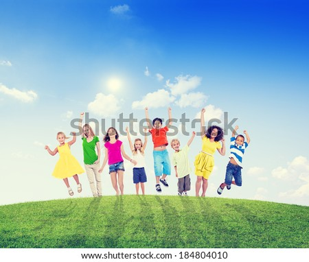 Cheerful Multi-Ethnic Children and Women Jumping On Hill