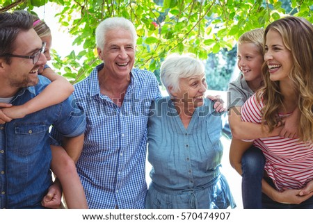 Cheerful multi generation family with parents giving piggy back standing against tree