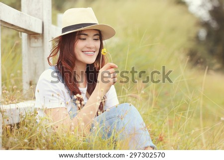 Cheerful multiracial Asian woman wearing a hat and  smelling flower in the grassland, red soft tone - stock photo
