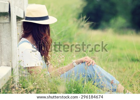 Cheerful multiracial Asian woman wearing a hat in the grassland, loneliness moment and vintage tone - stock photo