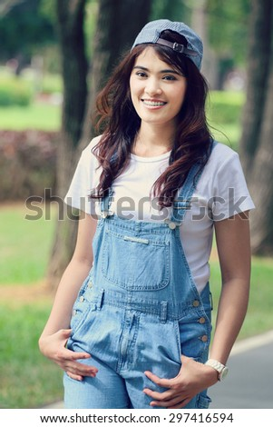 Cheerful multiracial Asian woman wearing a hat, vintage tone - stock photo