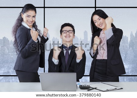 Cheerful multiracial businesspeople expressing their success in the office with laptop on desk - stock photo