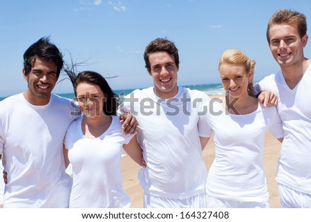 cheerful multiracial friends at the beach - stock photo