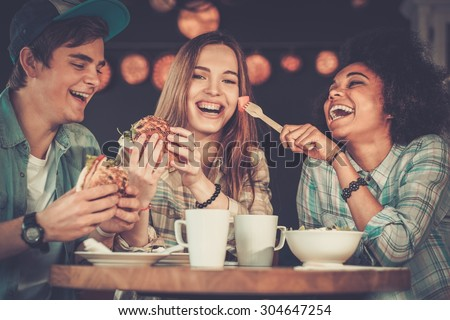Cheerful multiracial friends eating in a cafe  - stock photo