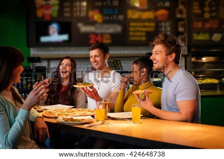 Cheerful multiracial friends having fun eating pizza in pizzeria. - stock photo