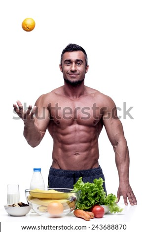 Cheerful muscular man standing with healthy food - stock photo