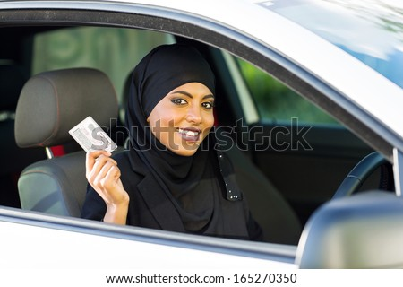 cheerful muslim woman showing a driving license she just got - stock photo