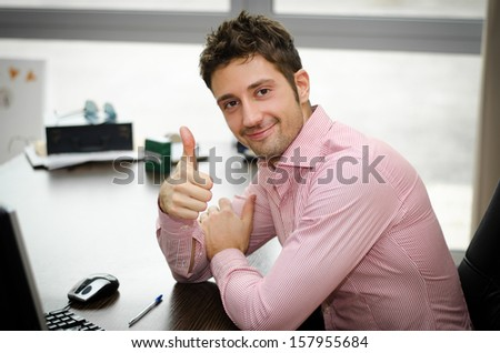 Cheerful office worker at desk doing thumb up sign and smiling. Real workplace - stock photo