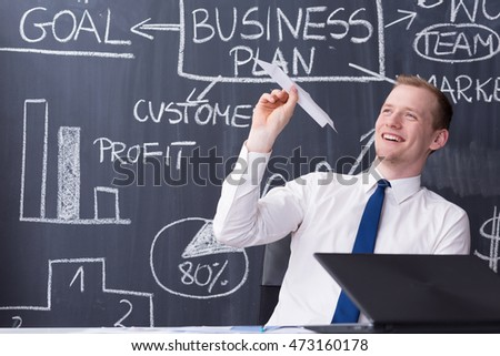 Cheerful office worker throwing a paper plane in front of a blackboard filled with graphs