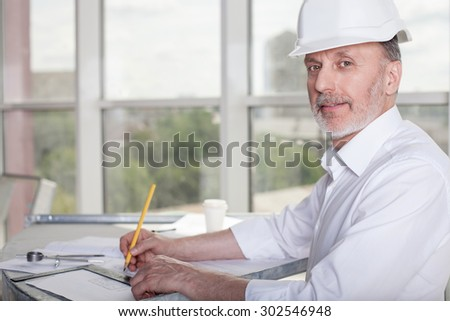 Cheerful old architect is sitting at the table and drawing sketches of building. He is looking at the camera and smiling - stock photo