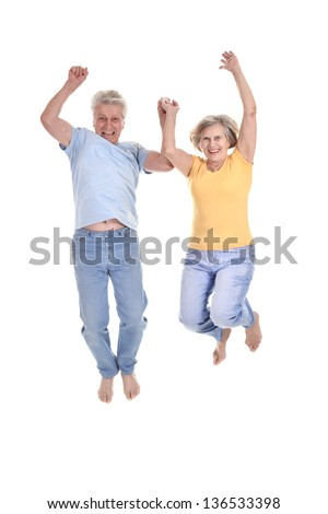 cheerful old couple jumping on a white background - stock photo