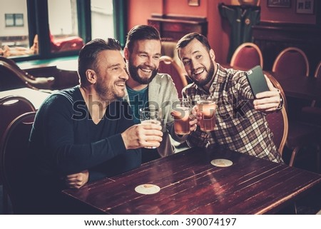 Cheerful old friends having fun taking selfie and drinking draft beer in pub.
