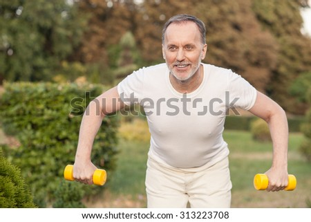 Cheerful old man is exercising in park. He is standing and holding dumbbells. The man is looking forward and smiling - stock photo