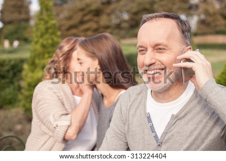 Cheerful old married couple and their daughter are sitting on bench outdoors. They are relaxing and smiling. The man is talking on the phone with joy. The mother and daughter are gossiping - stock photo
