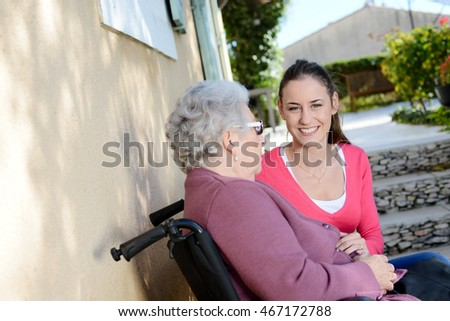 cheerful old woman in wheelchair with her young granddaughter outdoor in hospital