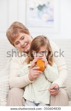 Cheerful old woman is looking after small granddaughter. She is sitting on couch and holding a comb. The grandmother is smiling. The girl is drinking juice with concentration - stock photo