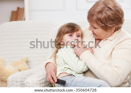Cheerful old woman is taking care of her granddaughter. She is sitting on sofa and holding a child. The grandmother comforting little girl - stock photo