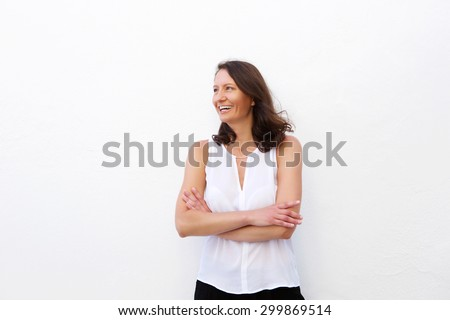 Cheerful older woman laughing with arms folded against white background - stock photo