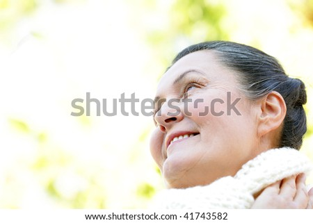 Cheerful older woman looking away toward the future on a crisp autumn day