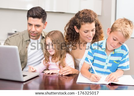 Cheerful parents colouring and using laptop with their children at home in kitchen