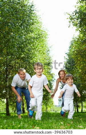 Cheerful parents release children to run in park - stock photo