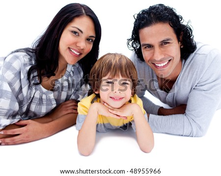 Cheerful parents with their son lying on the floor against a white background