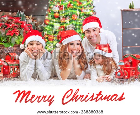 Cheerful parents with two cute smiling kids lying down near Christmas tree at home, festive greeting card with text space, happy family celebrating winter holidays