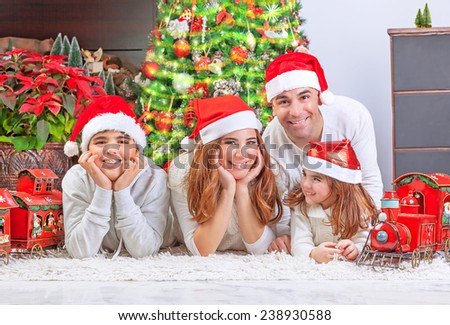 Cheerful parents with two cute smiling kids lying down near Xmas tree at home, celebrating Christmas, festive greeting card, happy family holiday concept - stock photo