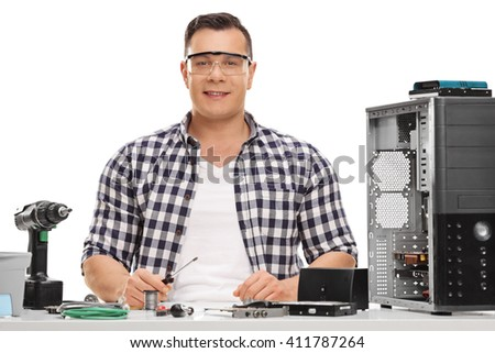 Cheerful PC technician sitting at a table and repairing a computer isolated on white background - stock photo