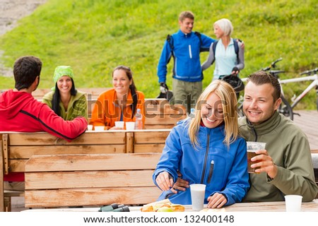 Cheerful people enjoying springtime weekend in rest area drinking beer - stock photo