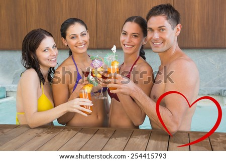 Cheerful people toasting drinks in the swimming pool against heart