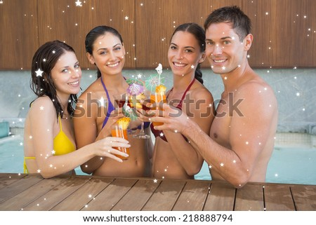 Cheerful people toasting drinks in the swimming pool against snow - stock photo
