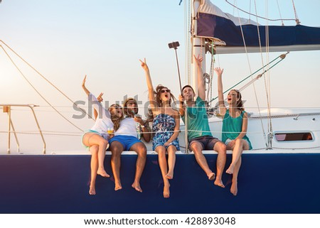 Cheerful people with selfie stick. Men with women on yacht. Remember this moment. Happiness that comes from heart. - stock photo