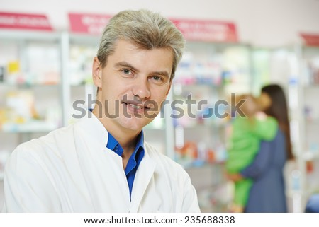 cheerful pharmacist chemist man in pharmacy drugstore - stock photo