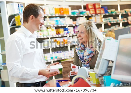 cheerful pharmacist chemist man worker standing at pharmacy drugstore desk with colleague - stock photo