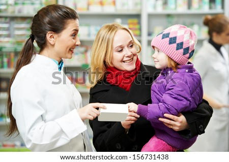 Cheerful pharmacist chemist woman demonstrating vitamins to child girl in pharmacy drugstore - stock photo