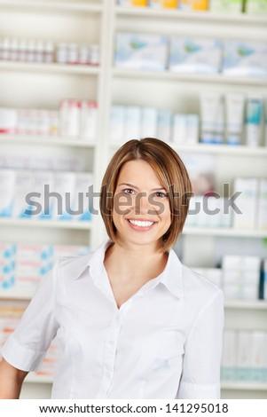 Cheerful pharmacist chemist woman standing in pharmacy drugstore - stock photo